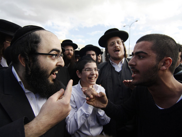 An ultra-Orthodox Jewish man (L) argues with a secular man during a protest against the government's pledge to curb Jewish zealotry in Israel, in the town of Beit Shemesh, near Jerusalem December 26, 2011. Israeli police arrested several ultra-Orthodox protesters on Monday after an officer was injured in the demonstrations in the divided city over demands by zealots to restrict access by women to certain streets.