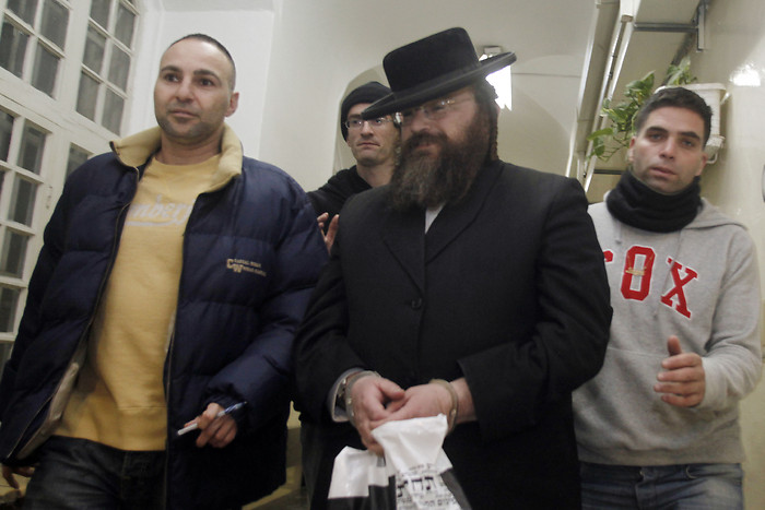 Amram Shapira, one of six ultra orthodox Jewish men arrested suspected of carrying out tax offenses involving millions of shekels, seen escorted by police in the Magistrate's Court in Jerusalem.